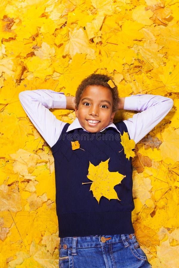 Gentil garçon heureux dans des feuilles d'érable d'automne photo stock