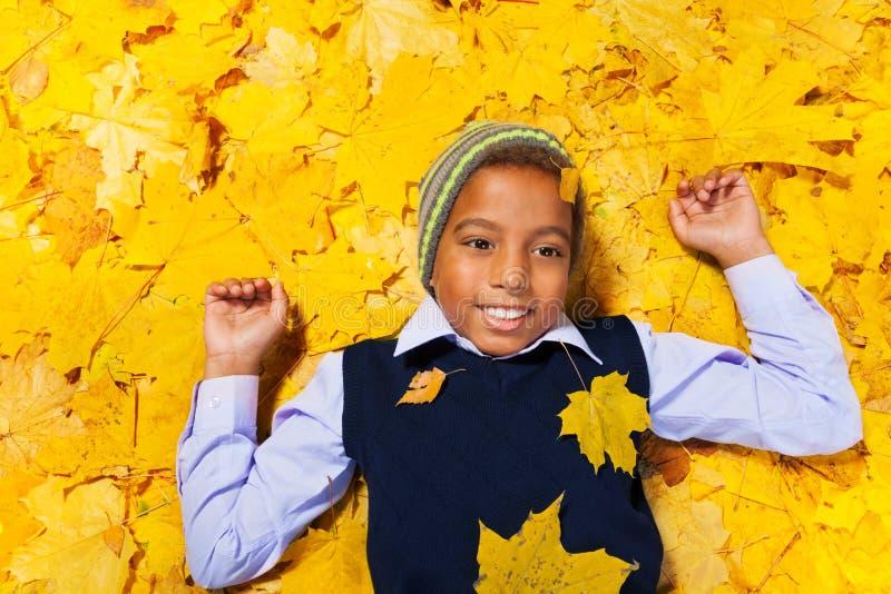 Gentil garçon noir s'étendant sur les feuilles d'automne en parc photos stock