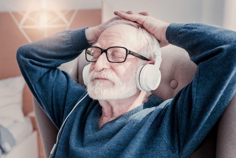 Gentil homme âgé fermant ses yeux photographie stock libre de droits