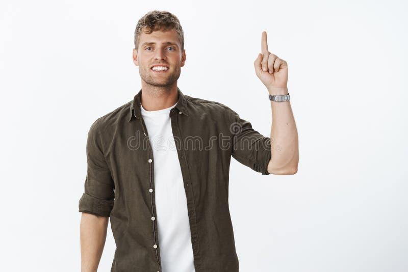 Gentil homme avec du charme avec les cheveux justes, les yeux bleus et le sourire blanc parfait se dirigeant avec la main augment images libres de droits