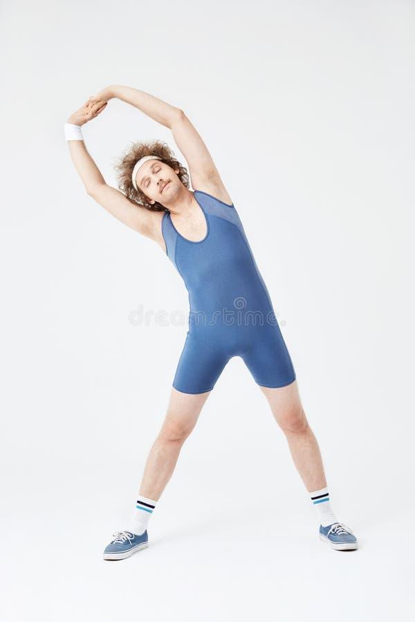 Gentil homme dans l'équipement de sport étirant les muscles du dos, semblant décontractés photo libre de droits