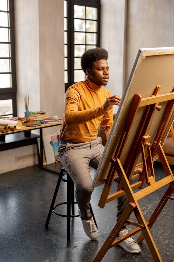 Gentil homme doué s'asseyant devant sa peinture photos libres de droits
