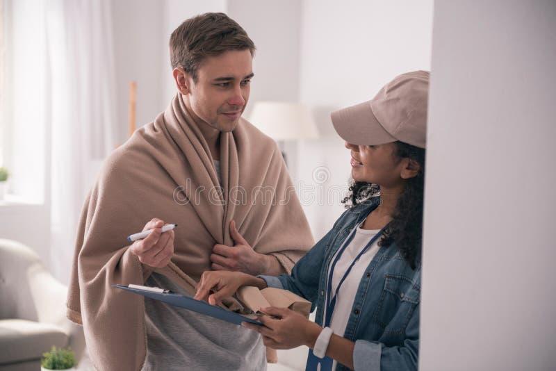 Gentil homme malade regardant la femme de la livraison photos stock
