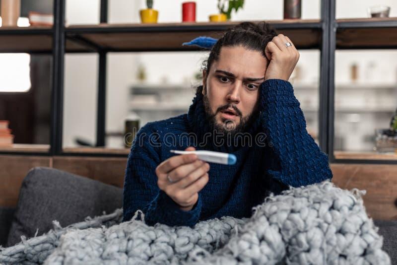 Gentil homme malade sombre vérifiant son thermomètre images libres de droits