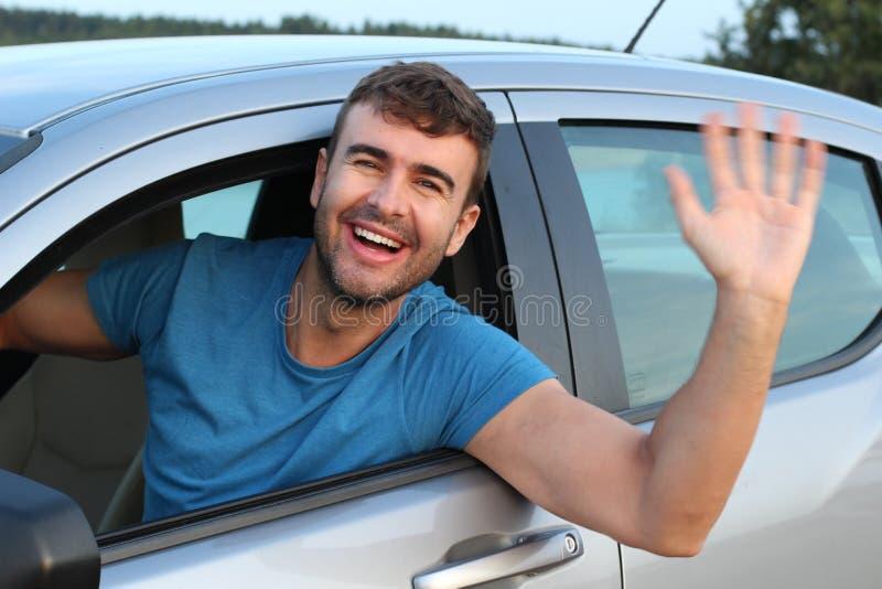 Gentil homme saluant quelqu'un tout en conduisant photographie stock