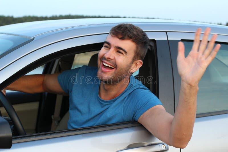 Gentil homme saluant quelqu'un tout en conduisant image stock