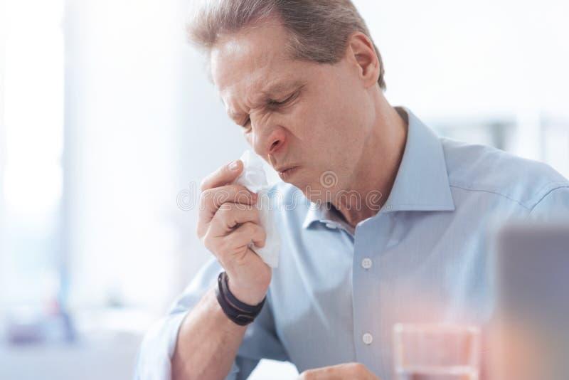 Gentil homme sombre essuyant son nez images libres de droits