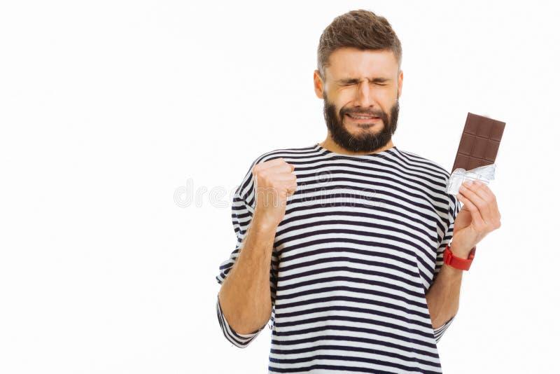 Gentil jeune homme essayant de ne pas manger du chocolat image libre de droits