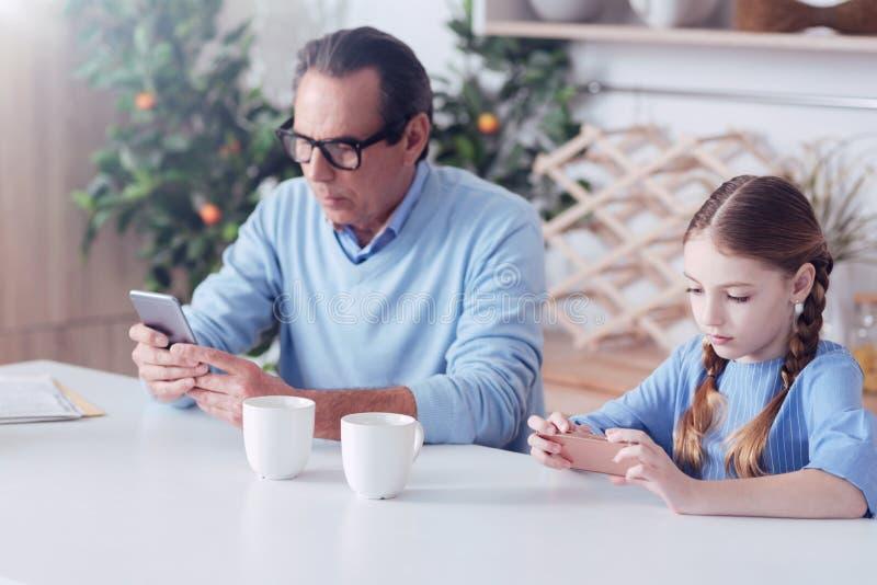 Gentil père et fille sérieux ne prêtant aucune attention entre eux images stock