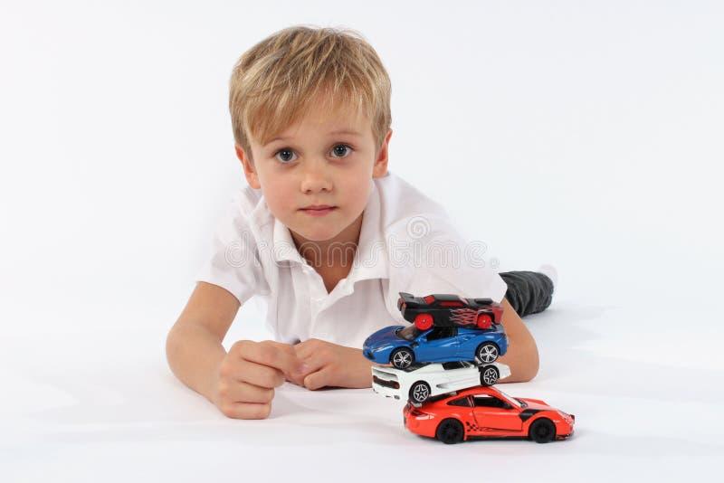 Gentil regardant le garçon très jeune se trouvant avec une pile des jouets de voiture et allant voir un neutre sincère et fier da photographie stock