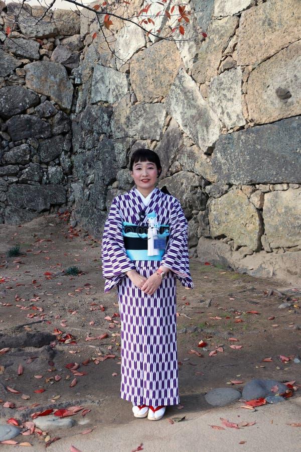 Gentile e piacevole del receptionist in vestito dal kimono su colore porpora e bianco al castello di Himeji fotografia stock libera da diritti