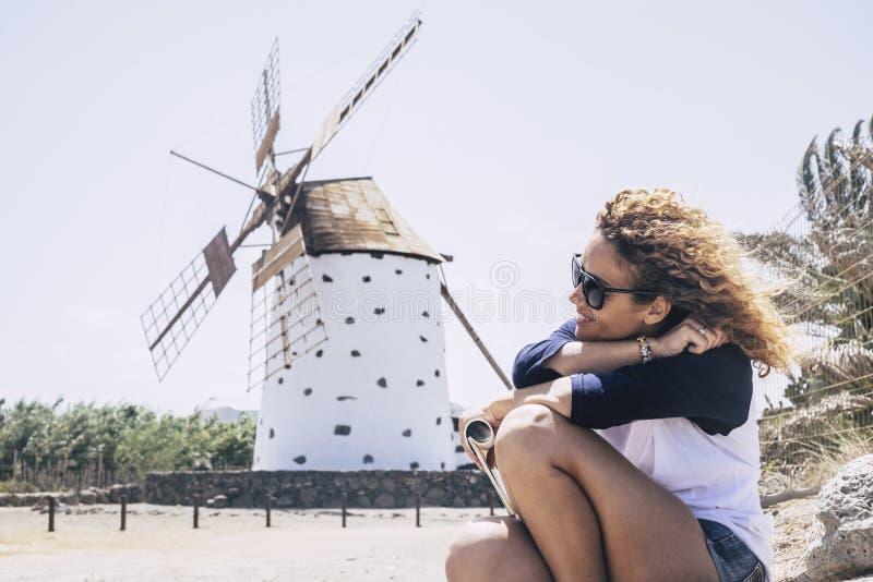 Gentille dame bouclée s'asseyant et détendant avec le sind dans les cheveux et un moulin de vent sur le fond endroit scénique de  photo stock