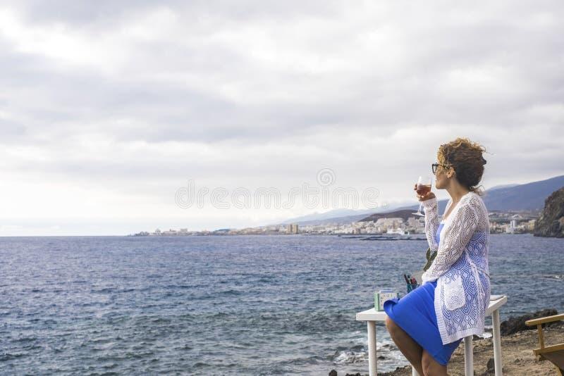 Gentille dame s'asseyant sur un bureau devant le vin potable d'océan bureau alternatif et emplacement de travail pour le nomade n photos libres de droits