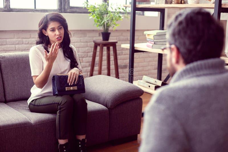 Gentille femme agréable partageant ses problèmes avec un thérapeute image stock