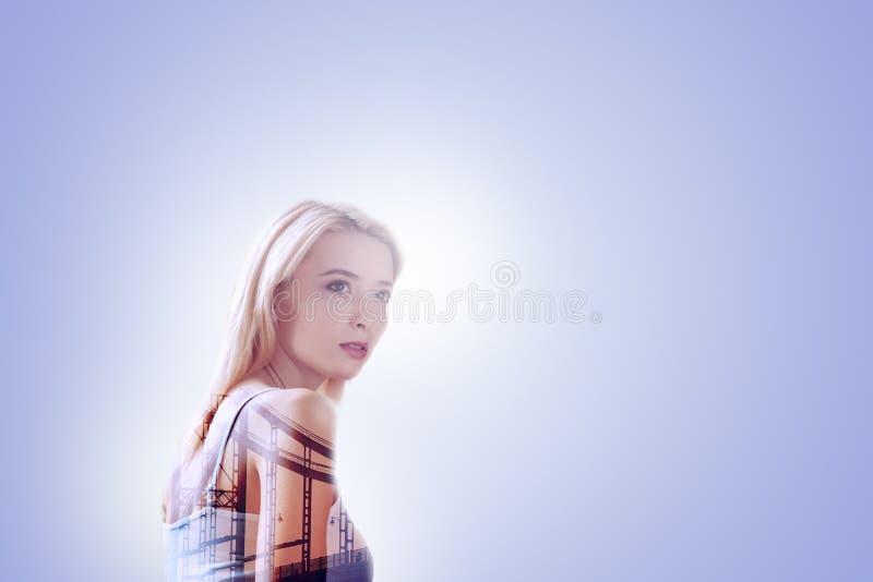Gentille femme attirante se tenant sur le fond bleu photos libres de droits