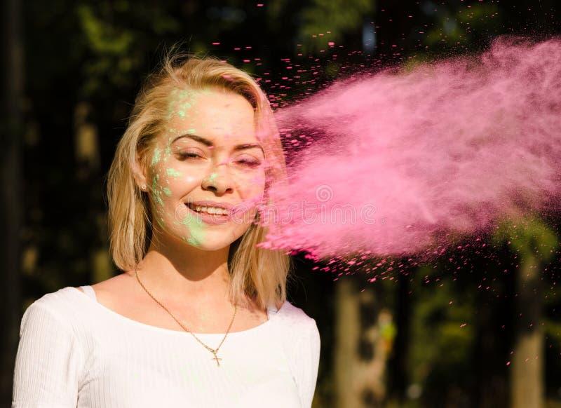 Gentille femme blonde dans le T-shirt blanc avec le nea de explosion de Holi de peinture photo stock