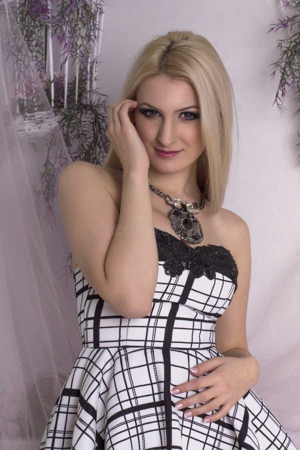 Gentille femme blonde dans une robe au studio photos stock