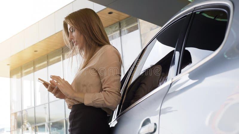 Gentille femme d'affaires appelle le client sur le smartphone, automobile proche debout photo libre de droits