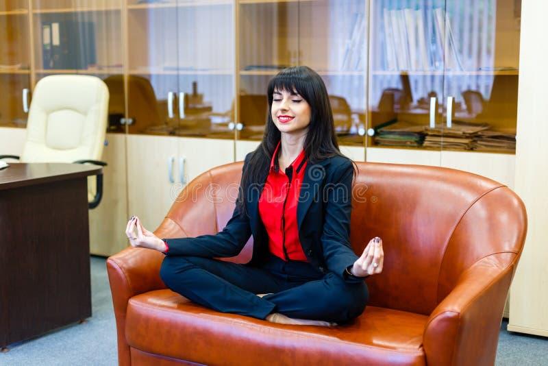 Gentille femme d'affaires de sourire s'asseyant sur le sofa dans le positi de lotus images libres de droits