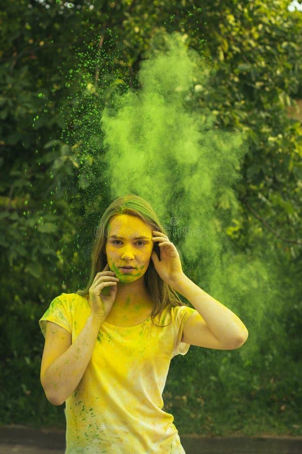 Gentille femme de brune avec éclater la poudre sèche verte photographie stock libre de droits