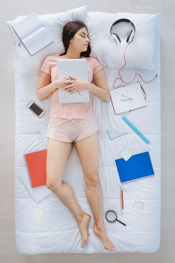 Gentille femme futée dormant avec son ordinateur portable photos libres de droits