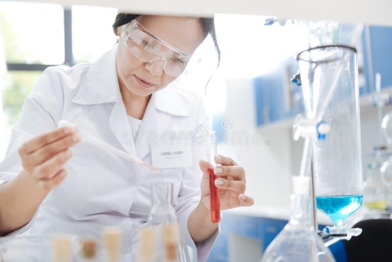Gentille femme futée mettant le réactif chimique dans un flacon images stock