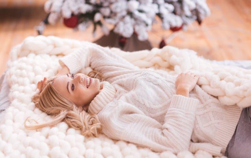 Gentille femme heureuse se trouvant sur le plaid tricoté images stock