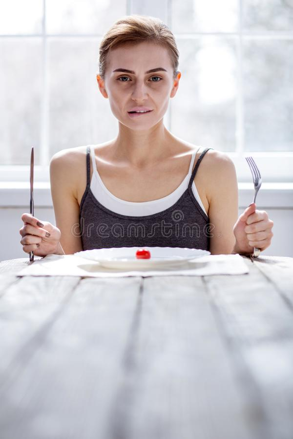 Gentille femme pâle tenant une fourchette et un couteau images stock
