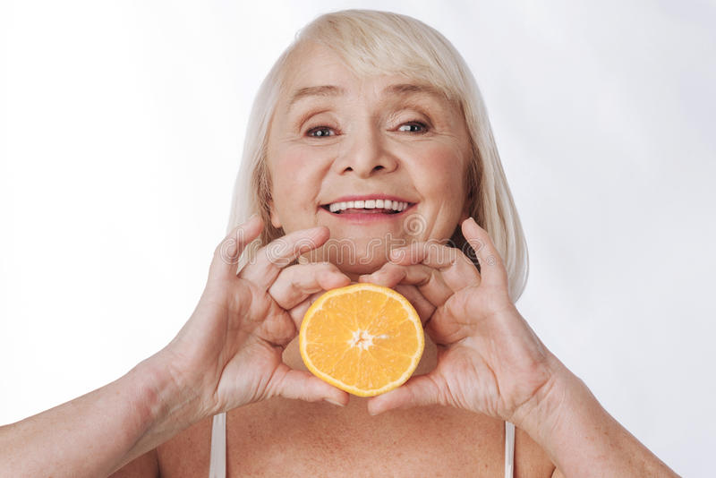 Gentille femme satisfaite tenant une orange images stock