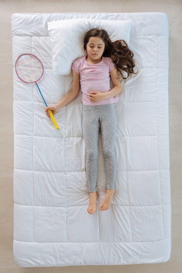 Gentille fille agréable ayant un rêve au sujet d'un jeu de badminton image libre de droits