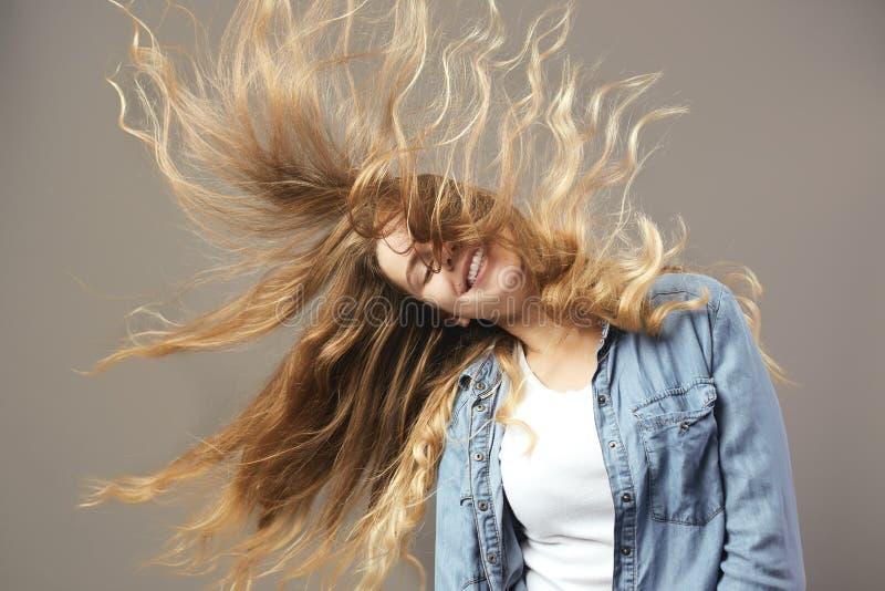 Gentille fille avec de longs sourires débordants bruns de cheveux sur un fond gris image stock