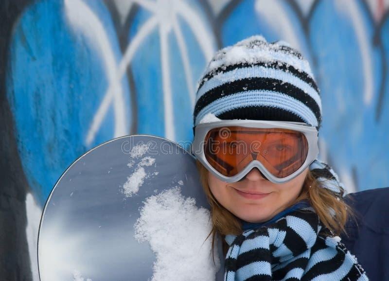 Gentille fille avec le snowboard, fond de graffiti. photographie stock libre de droits