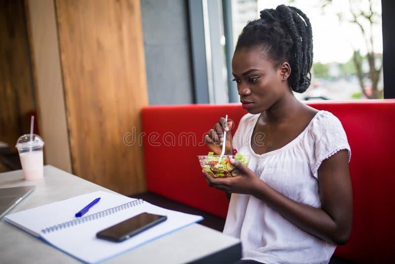 Gentille fille d'Afro-américain mangeant dans le restaurant Fille de sourire s'asseyant au café et regardant avec de la salade su photos stock