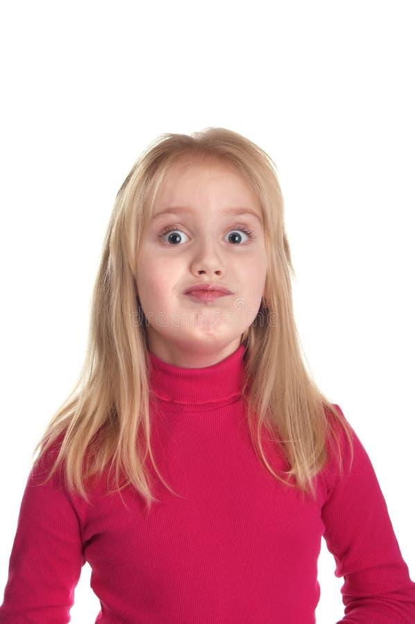Gentille fille dans les grimaces ridicules d'un chandail rose image stock
