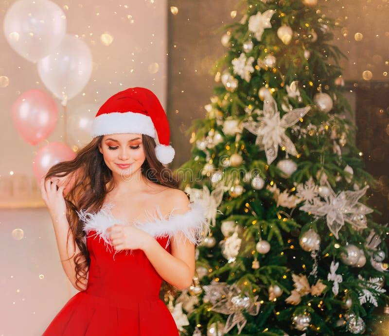Gentille fille de Wonderfull dans une robe rouge de Santa Claus de l'écarlate de nouvelle année, regard vers le bas et souriant g photographie stock