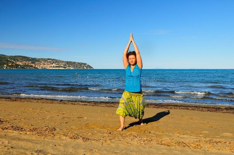 Gentille fille faisant l'exercice de yoga sur la plage image stock