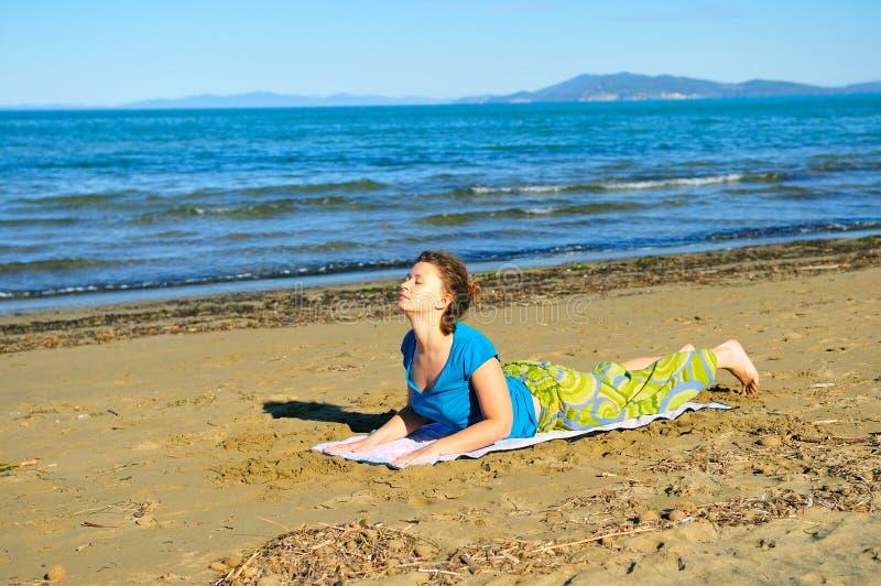 Gentille fille faisant l'exercice de yoga sur la plage image libre de droits