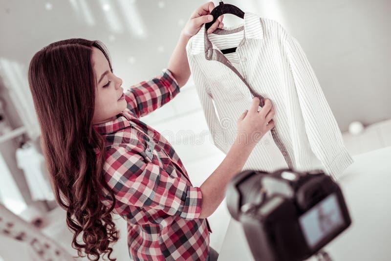 Gentille fille joyeuse tenant un cintre avec sa chemise photographie stock