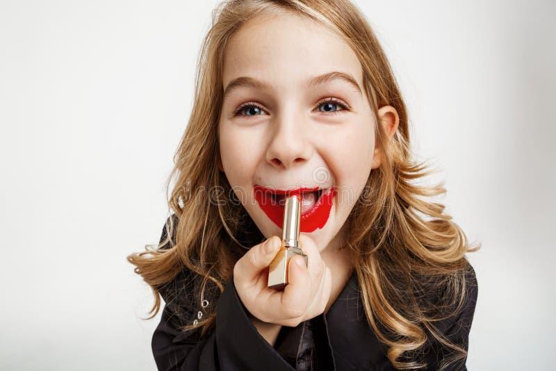 Gentille fille mettant sur le rouge à lèvres de rouge du ` s de mère Peut le ` t faire face à composent Regard drôle images stock