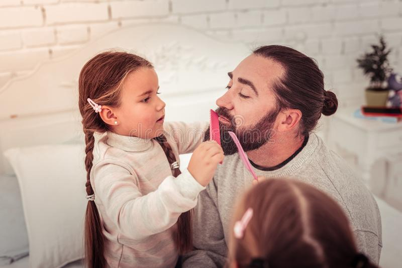 Gentille fille mignonne peignant sa barbe de papas photographie stock libre de droits