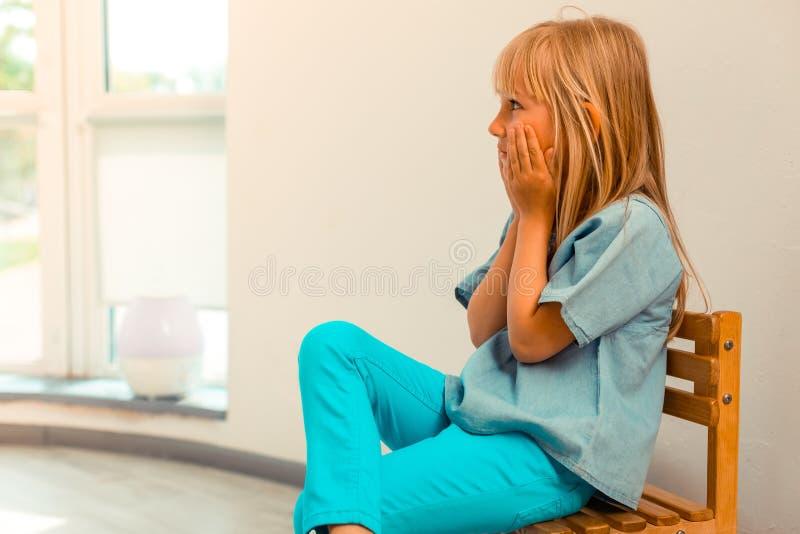Gentille fille mignonne s'asseyant sur la chaise images stock