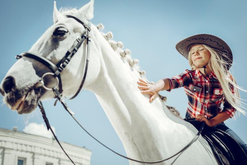 Gentille fille mignonne touchant un cheval blanc photo stock