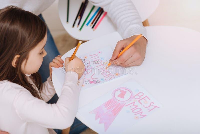 Gentille fille positive préparant une carte postale au jour de mères photographie stock libre de droits