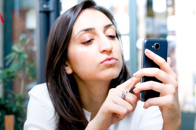 Gentille fille regardant son téléphone et touchant l'écran photos stock