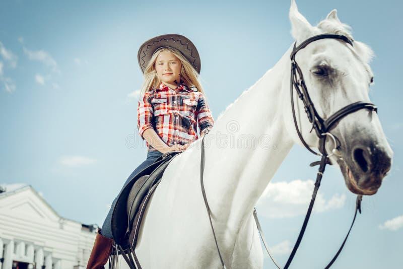 Gentille fille s?re s'asseyant sur le cheval photographie stock