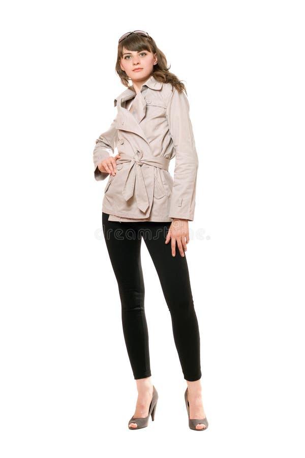 Gentille fille utilisant un manteau et des guêtres noires D'isolement photos libres de droits
