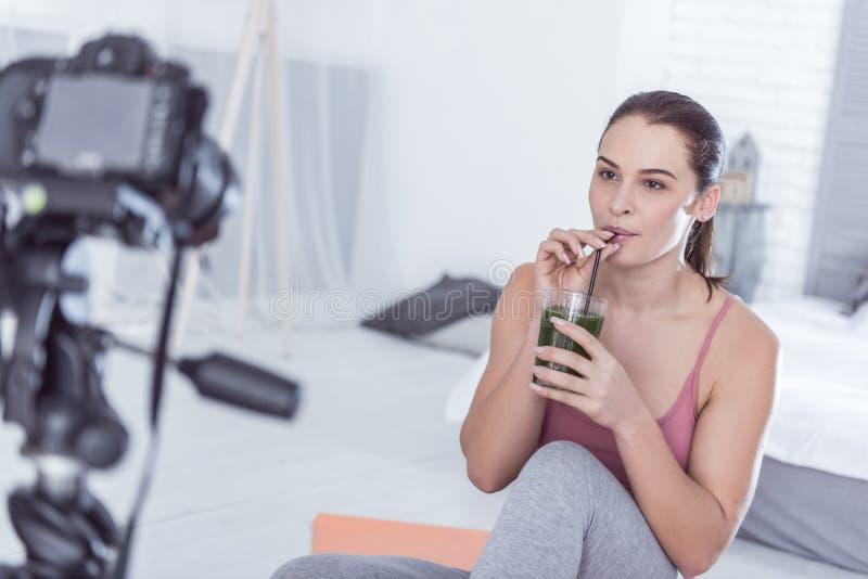 Gentille jeune femme avec plaisir buvant le smoothie sain photo stock
