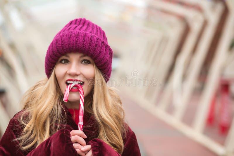 Gentille jeune femme blonde dans le chapeau tricoté par rouge posant avec la boîte de sucrerie images libres de droits