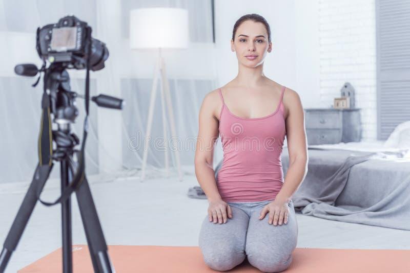 Gentille jeune femme s'asseyant devant l'appareil-photo photographie stock libre de droits