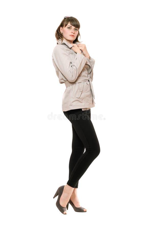 Gentille jeune femme utilisant un manteau et des guêtres noires photos stock